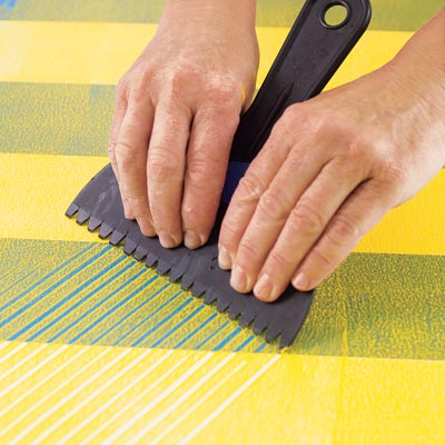 combing the herringbone pattern with a modified plastic putty knife