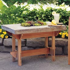 a hypertufa table next to a deck chair on a patio