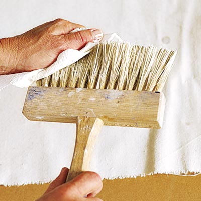 wiping excess glaze from the stiff-bristled brush with a clean rag