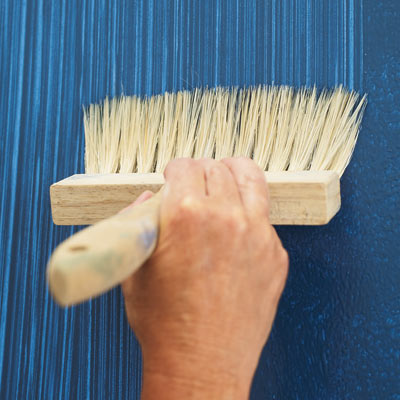 applying blue glaze faux fabric with a stiff-bristled brush