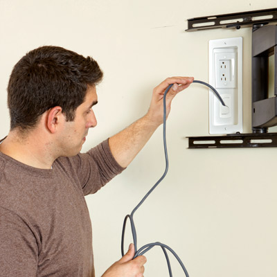 inserting cables for hanging a flat-screen tv