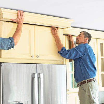 mounting the hardwood frame with crown molding attached to the top of a kitchen cabinet