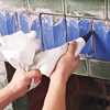 photo of grout being applied to art tiles with a grout bag