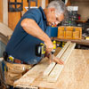Tom Silva uses a paddle bit to enlarge the pilot holes to the size of the baluster pins