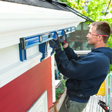 installer Peter Robinson makes sure the gutter slopes during installation of fiberglass gutters