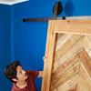 hoisting the sliding barn door onto the sliding track