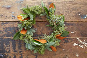 evergreen wreath made with evergreen clippings and magnolia leaves on a distressed wood table