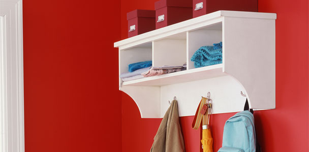 a completed white cubby shelf with three storage boxes resting on the top, clothing and papers in the cubbies, and personal accessories hanging from the hooks, installed on a red wall