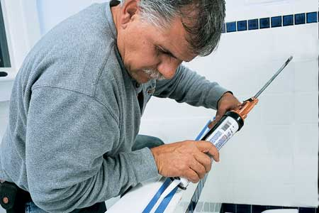 tom silva bent over a tub using a caulk gun to lay a bead along the line where tile meets tub