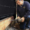 Tom Silva attaching the ledger of an on-grade deck