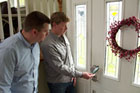 Kevin O'Connor helps a homeowner install an electronic deadbolt