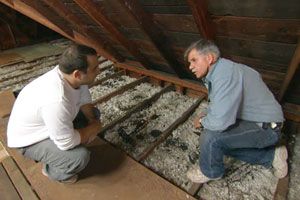 Tom Silva measures the depth of the existing blown-in insulation