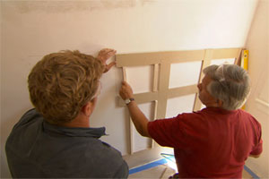 host Kevin O'Connor assists general contractor Tom Silva installing a row of wainscotting on an otherwise empty bathroom wall