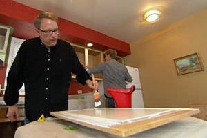 Kevin O'Connor helps a homeowner refinish his kitchen cabinets