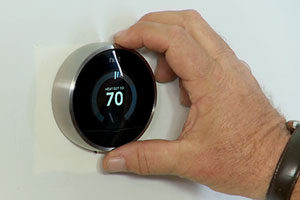 Richard Trethewey shows a homeowner how to install an energy-saving smart thermostat