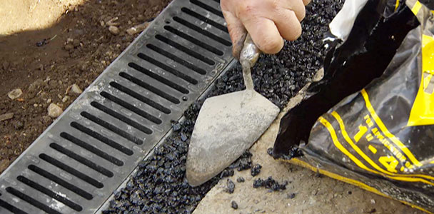 Roger Cook installs a channel drain