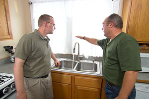 Richard Trethewey helps a homeowner install a no-touch kitchen faucet