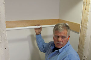 Tom Silva trims a coat closet by installing a clothes rod and shelf