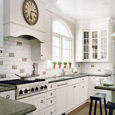 A kitchen with white painted glass front cabinets, beadboard accents and white light fixture  give a vintage look