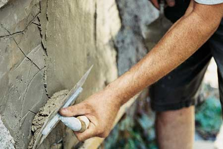 using a finishing trowel on second coat of stucco